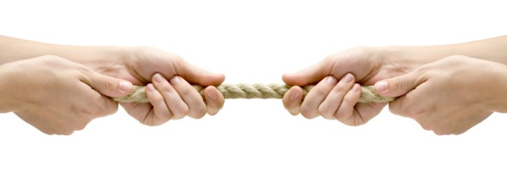 Two sets of hands playing tug of war with a short rope